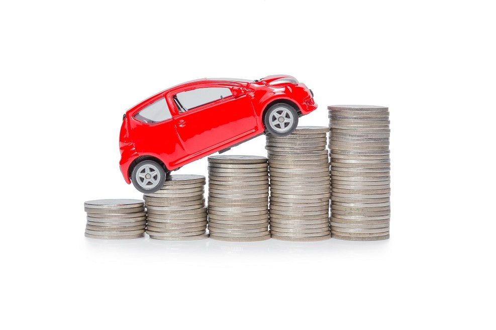 a car stand on a stack of coins isolated on white background